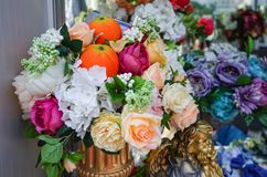 Flower arrangement of artificial flowers and oranges stock images