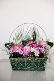 Flower arrangement in basket with ranunculus and small pink and. Flower arrangement in basket with dark and light pink ranunculus and austeria front view and Royalty Free Stock Photo