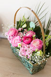 Flower arrangement in basket with ranunculus and small pink and. Flower arrangement in basket with dark and light pink ranunculus and austeria view from above Stock Photos
