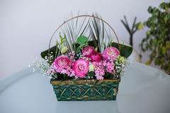 Flower arrangement in basket with ranunculus and small pink. Front view of flower arrangement in basket with dark and light pink ranunculus and austeria Royalty Free Stock Photography