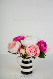 Flower Arrangement in Black and White Vase. A pink and white flower arrangement in a black and white striped vase with gold glitter sparkles Stock Images