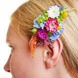 Flower arrangement in blond hair. Of a young woman royalty free stock photo