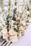Flower arrangement bouquet of pink roses, ranunculus and white bells and eucalyptus on a white background. Vertical royalty free stock photography