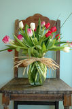 Flower Arrangement On Chair. Tulips delivered from the local florist sitting in an eggshell blue interior on an antique chair Stock Images
