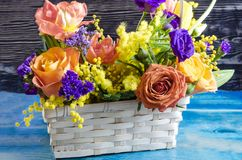 Flower arrangement close-up of fresh flowers of red yellow blue orange flowers in a wicker basket stock images