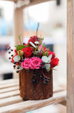 Flower arrangement close-up. Flower arrangement of multi-colored roses and berries in wooden stump, floristic art close-up Royalty Free Stock Image