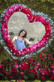 Flower arrangement, decor, design. Young girl pose in floral heart, spring. Love symbol, romance. Happy valentines day concept. Child smile in flower frame on stock photos