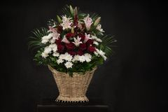 Ritual funeral basket with flowers on a black background. The flower arrangement of the flowers in the basket is used for funerals and bookmarks. Mourning card royalty free stock photo