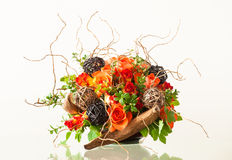 Flower arrangement. Ikebana-like artistic flower arrangement in a container on a glossy table Royalty Free Stock Photo