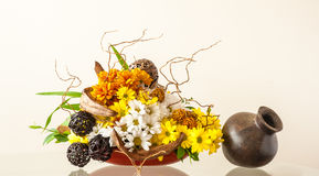Flower arrangement. Ikebana-like artistic flower arrangement in a container on a glossy table Stock Image