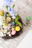 Flower arrangement in a nest with easter eggs on a white table Stock Photography