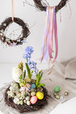Flower arrangement in a nest with easter eggs on a white table Royalty Free Stock Image