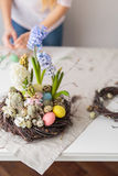 Flower arrangement in a nest with easter eggs on a white table Royalty Free Stock Photo