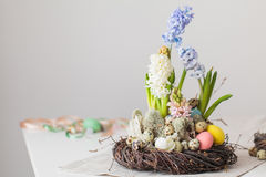 Flower arrangement in a nest with easter eggs on a white table Stock Photos