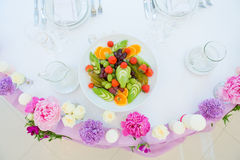 Flower arrangement pink violet lilac colors. Decoration flower arrangement pink violet lilac colors white tablecloth Royalty Free Stock Image