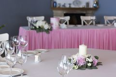 Flower arrangement in pink with white candles on the festive table on the wedding day. stock photo