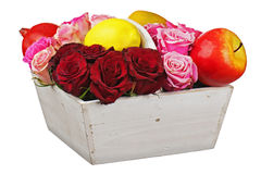 Flower arrangement of red roses and fruits in wooden basket isol Stock Photography