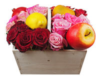 Flower arrangement of red roses and fruits in wooden basket isolated on white background. stock image