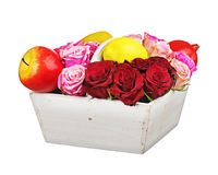 Flower arrangement of red roses and fruits in wooden basket isol Royalty Free Stock Photography