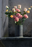Flower arrangement with romantic mood. Romantic arrangement of dahlia flowers in an iron vase Stock Image
