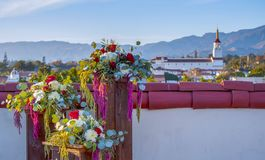 Flower Arrangement on Rooftop with Santa Barbara California Skyl. Arrangements of flowers sit on pedestals on a rooftop in Santa Barbara.  Some of the city and Royalty Free Stock Images