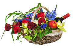 Flower arrangement of roses, orchids, fruits and bottle of wine Stock Image