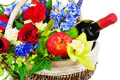 Flower arrangement of roses, orchids, fruits and bottle of wine Royalty Free Stock Photos