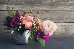 Flower arrangement of roses and ranunculus. With candles on shabby wooden background. Greeting card concept royalty free stock images