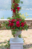 Flower arrangement in stone bowl with red roses Stock Images