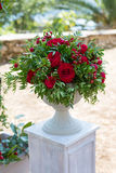 Flower arrangement in stone bowl with red roses Stock Photos