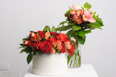 Flower arrangement on table. Bouquet of roses in a paper box. vase in the background Stock Photography