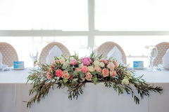 Flower arrangement on the table. Flowers and white tablecloth, wedding, roses, peonies. Flower arrangement on the table. Flowers on a white tablecloth, roses and Royalty Free Stock Image