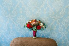 Flower arrangement for a wedding party. The bouquet of pink roses, red peonies, and other flowers on blue wall Stock Photography