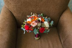 Flower arrangement for a wedding party. The bouquet of pink roses, red peonies and other flowers on brown armchair Royalty Free Stock Photography