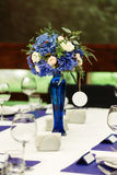 Flower arrangement on wedding table. Floral compositions with fresh roses and blue flowers Royalty Free Stock Photography