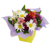 Flower arrangement in yellow paper box isolated on white. Fresh bouquet with gerbera and alstroemeria. Colorful flowers isolated Stock Images