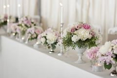Перевести вGoogleBingFlower arrangements are on the table covered with a white tablecloth. Silver candlesticks. Flower royalty free stock image