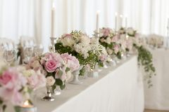 Перевести вGoogleBingFlower arrangements are on the table covered with a white tablecloth. Silver candlesticks. Flower stock image