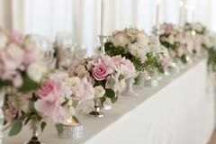 Перевести вGoogleBingFlower arrangements are on the table covered with a white tablecloth. Silver candlesticks. Flower stock photo