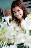 Flower Arranging. A pretty young woman arranging flowers in the kitchen royalty free stock photo
