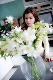 Flower Arranging. A pretty young woman arranging flowers in the kitchen Royalty Free Stock Photos