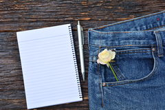 Flower in bag of denim jeans with notebook and pen, Denim jeans Royalty Free Stock Photo