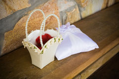 Flower Basket and Ring Pillow. A Flower Basket and Ring Pillow sit on a wooden bench Stock Images