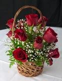 Flower basket on white tablecloth. Flower basket with red roses on white tablecloth Stock Photography