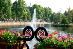 Circular geometric iron work frames a fountain in the background. Flower baskets and interesting iron work in the foreground frames a spouting fountain in the stock image