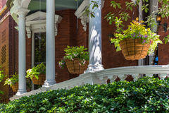 Flower Baskets on the Porch. Serveral flower baskets with foliage hanging from a porch with white pillar columns on a brick house Stock Images