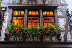 Flower bed of flowers on the window facade of the old house in europe . France Stock Photo