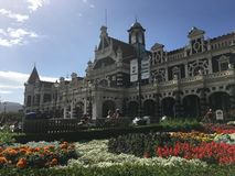 Flower bed outside Dunedin Railway Station. Flower beds outside Dunedin Railway Station against blue skies in New Zealand Stock Images