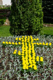 A flower bed with yellow flowers in the form of an Orthodox cross. Stock Image