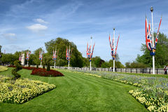 Flower Beds in Buckingham Palace Garden Mall. Colorful Landscaped Flower Beds in Mall of Buckingham Palace Garden Lined with British Flags, London, England Royalty Free Stock Images